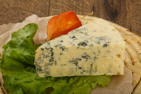 roquefort: Blue cheese with salad leaves over the wooden background Stock Photo