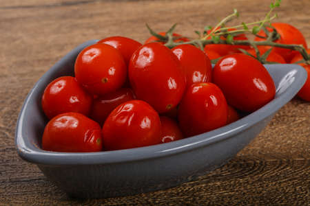 Pickled cherry tomatoes heap on the wooden background