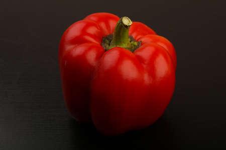 Rode paprika over de zwarte houten achtergrond