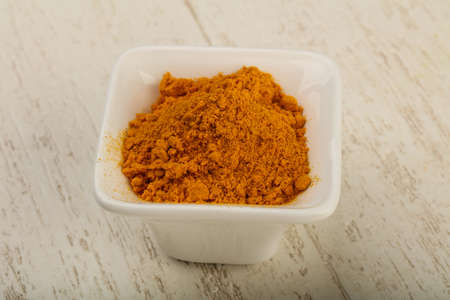 tumeric: Curcuma powder in the bowl over wooden background