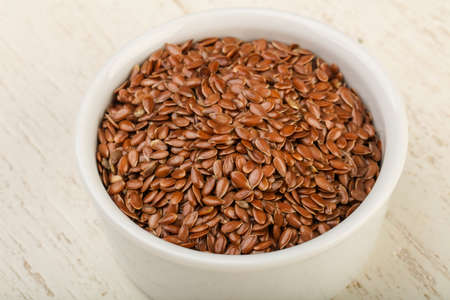 linseed: Fry Flax seeds heap in the bowl over wooden background
