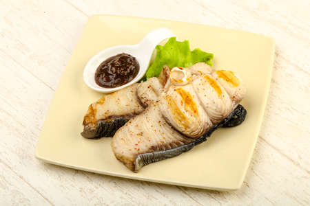 Grilled shark steak with pepper sauce and salad leaves