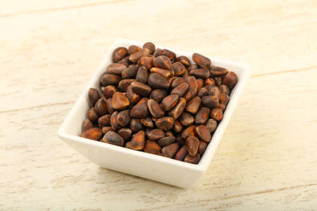 Cedar nuts heap in the bowl over wooden background Stock Photo
