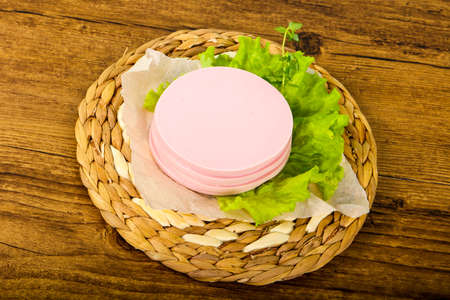 Sliced sausage with salad leaves over the wooden background Stock Photo - 83952819
