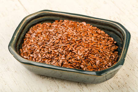 linum: Fry Flax seeds heap in the bowl over wooden background