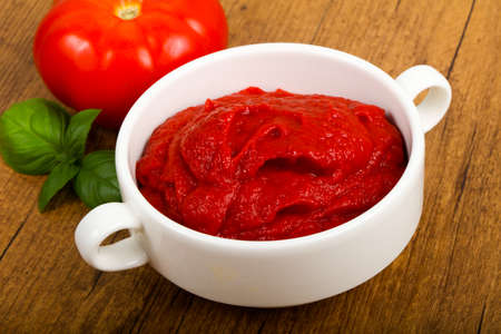 Tomato paste with basil leaves Stock Photo