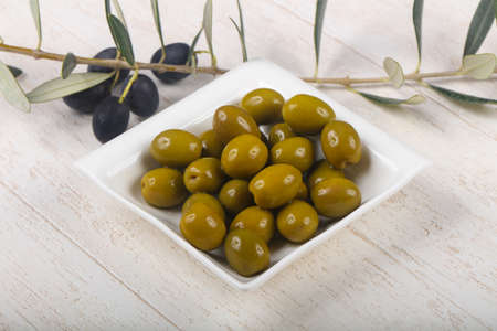 heap: Green olives in the bowl served branch