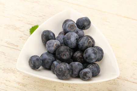 heap: Blueberry in the bowl over the wooden background