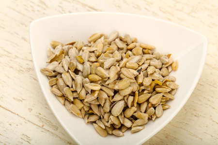 heap: Peeled sunflower seeds heap over the wooden background Stock Photo