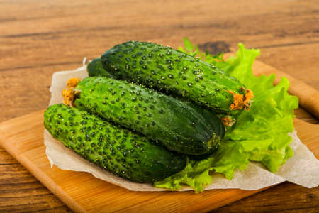 Green cucumbers with salad leaves over the wooden background