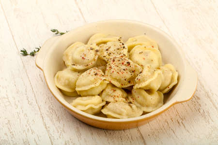 Russian dumplings in the bowl with pepper and butter