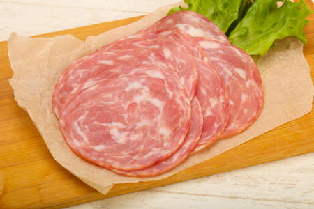 Sliced sausage with salad leaves Stock Photo - 88784014