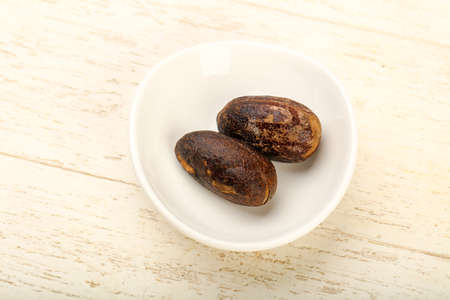 Two Nutmegs for culinare use over wooden background Stock Photo