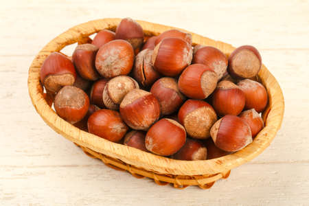 Hazelnut heap in the basket over wooden background