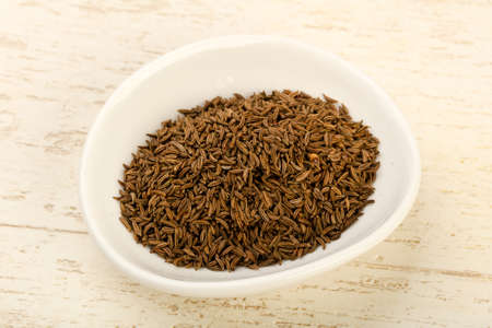 Caraway pile in the bowl over wooden background