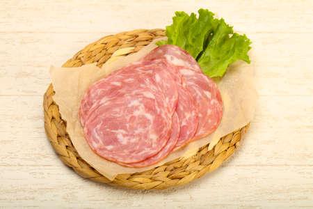 Sliced sausage with salad leaves