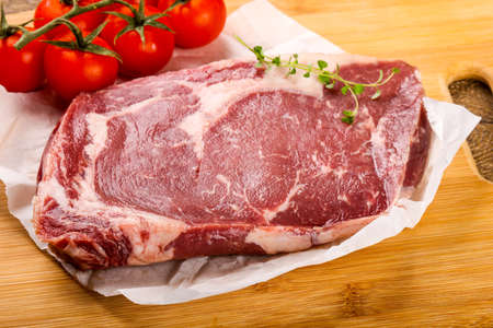 angus: Raw ribeye steak with thyme - ready for cooking