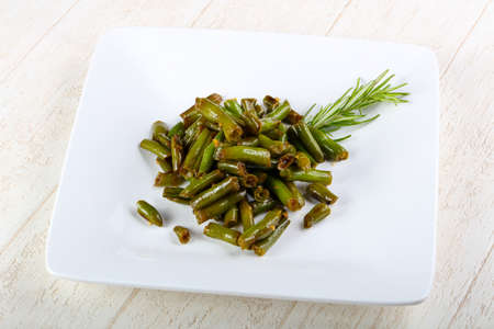 Baked green beans with rosemary on wood background Stock Photo