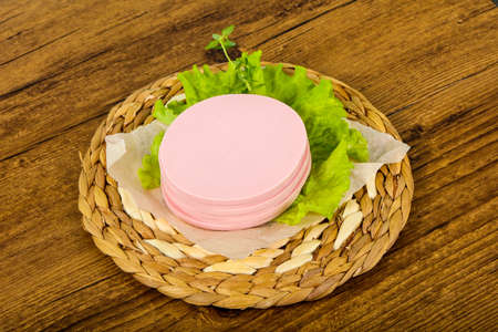 Sliced sausage with salad leaves over the wooden background