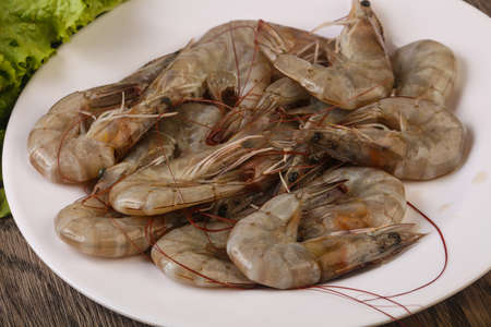 Raw king prawn heap in the bowl over wooden background