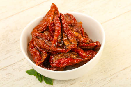 Dried tomato in olive oil with basil leaves
