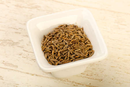 Cumin seeds heap in the bowl over wooden background
