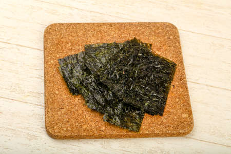 Crispy Nori sheets chips over wooden background Reklamní fotografie