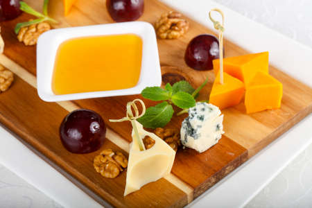 Cheese plate mix with grape, honey and nuts