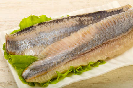 Herring fillet over salad leaves - ready for eat Stock Photo
