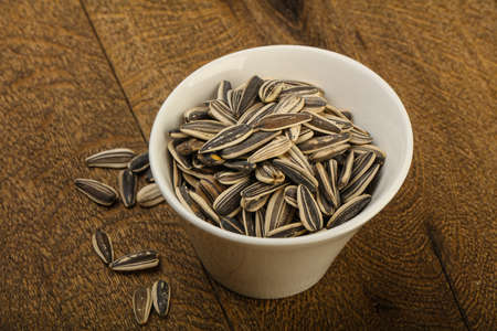 Sunflower seeds in the bowl over the wooden background