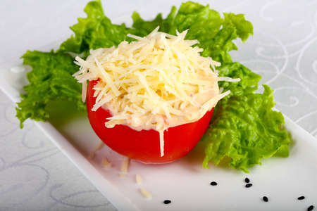 Stuffed tomato with cheese and garlic sauce