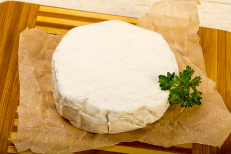 Camembert cheese with parsley over the wooden background Stock fotó