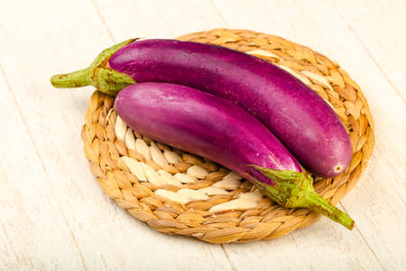 Raw violet eggplant on the wooden background