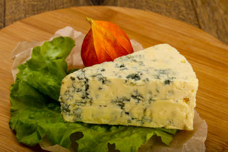 Blue cheese with salad leaves over the wooden background 写真素材