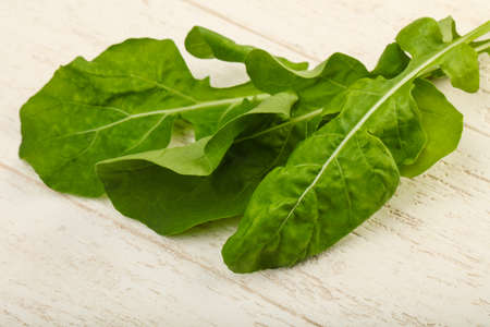 Fresh green Ruccola leaves over the wooden background