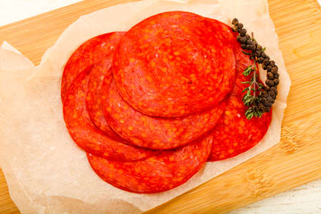 Sliced chorizo saucage over the wooden background Stock Photo