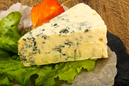 Blue cheese with salad leaves over the wooden background Stock Photo