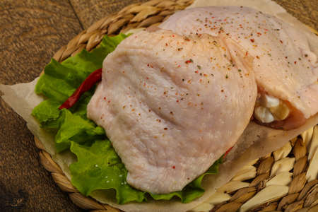 Raw chicken thigh with spices ready for cooking