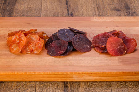 Dry meat snack over the wooden background