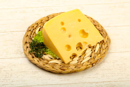 Piece of cheese over the wooden plate