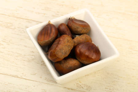 Chestnuts in the bowl over wooden background Archivio Fotografico