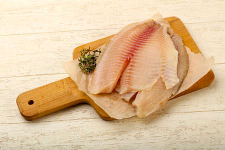 Tilapia fillet ready for cooking over wooden background