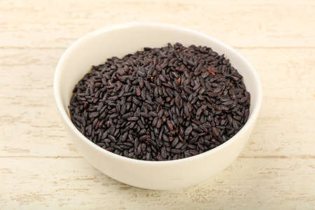 Black wild rice in the bowl over wooden background