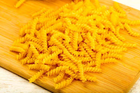 Raw fussili for pasta over the wooden background