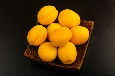 Ripe sweet apricots over the wooden background