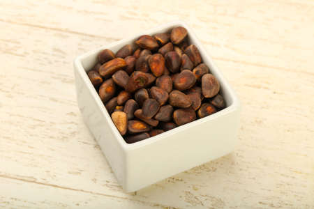 Cedar nuts heap in the bowl over wooden background 스톡 콘텐츠