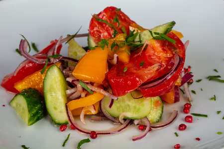 Tasty rustic salad with chopped tomatoes, cucumbers, onions and pepper