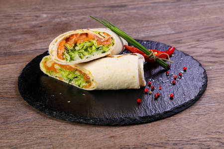 Salmon roll tortilla served onion and red pepper Imagens