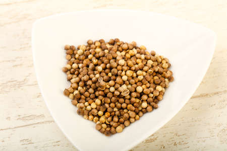 Coriander seeds heap over the wooden background Stock Photo