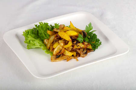 Fried potato with mushrooms served parsley